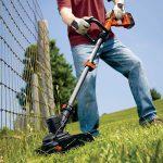 A man using the BLACK+DECKER GLC3630L20 to trim grass.