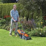 A happy man mowing his lawn with the Flymo Chevron 32VC.