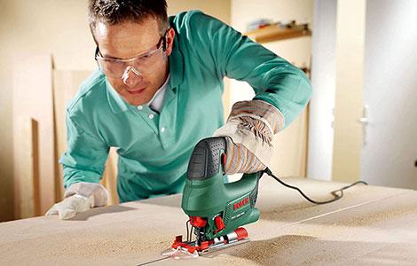 Man using a Bosch jigsaw to cut some wood.